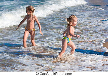 Little girls in the spray of waves at sea
