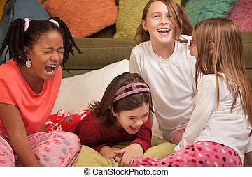 Group of four girls at a sleepover laugh out loud