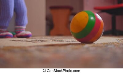 Little girl's legs with her pot, mom helping, the ball is in...