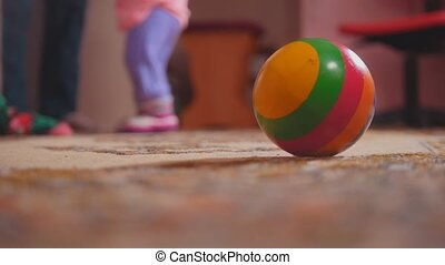 Little girl's legs with her toys, mom helping, the ball is...