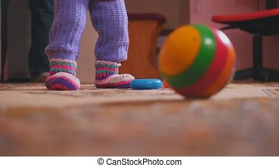 Little girl's legs with her toys, the colorful ball is in...
