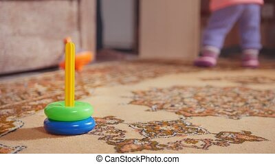 Little girl's legs with her toys, the colorful pyramid is in...