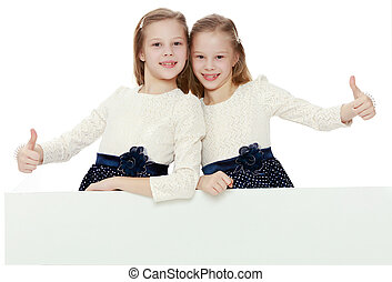 Little girls look out from behind the banner.