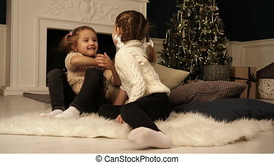 Little girls looking at each other posing during Christmas...