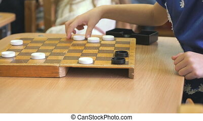 Little girls sit at the table and play checkers at the garden. Close-up