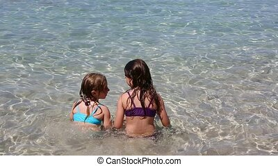 little girls playing in shore beach