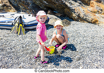 little girls playing on the beach at sea