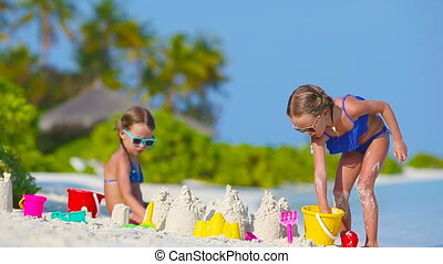 Little girls playing with beach toys during tropical...