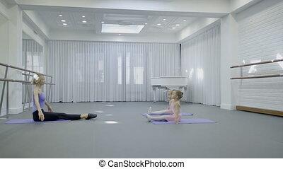 Little girls practice with teacher in ballet studio.