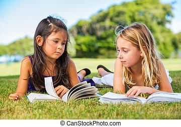 Little Girls Reading Books on Grass