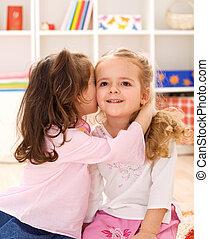 Little girls sharing a delightful secret