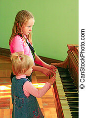 little girls sisters playing piano. Music lessons. Children try to play piano