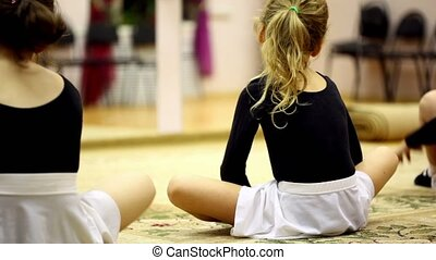 Little girls sit on floor and streches risen legs, view from behind