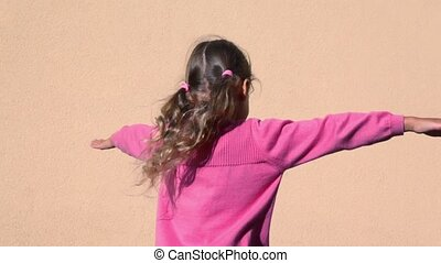 Little girls spins with arms up sideward near wall