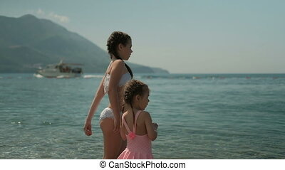 Little girls stand on beach and throw stones into water in sunny weather.