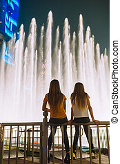 Little girls watch the legendary show of singing fountains in Dubai