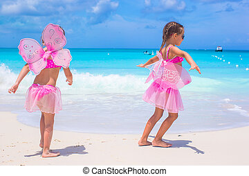 Little girls with butterfly wings have fun beach summer vacation