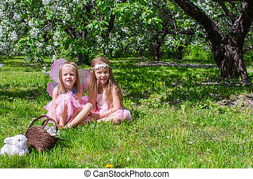 Little girls with butterfly wings in the blossoming apple orchard