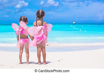 Little girls with butterfly wings on beach summer vacation
