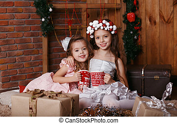 Little girls with Christmas knitted cups.