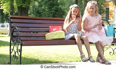 Little girls with lollipops having fun on a bench in summer