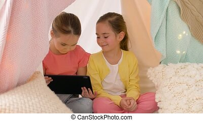 little girls with tablet pc in kids tent at home