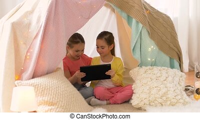 little girls with tablet pc in kids tent at home -...