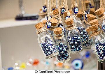 Little glass bottle filled with blue evil eye beads