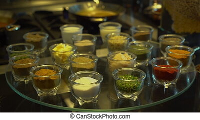 Little glasses with varied seasoning - A steady, medium shot...