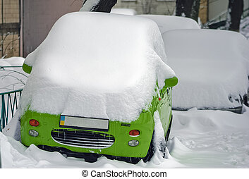 Little green car standing in the yard of a residential apartment building, all covered with snow.