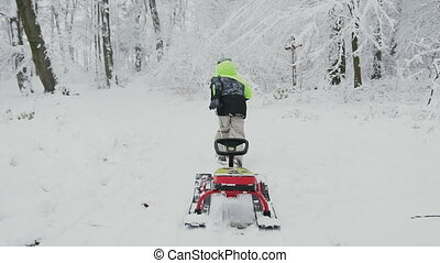 Little guy in light green with a black jacket and hat running on a snow-capped mountain and entails sled with a rudder. Winter holiday