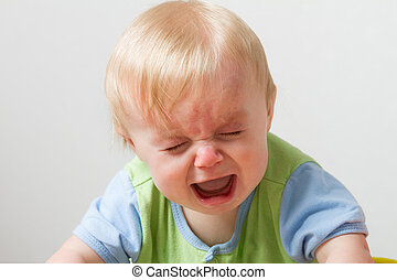 Young toddler crying away. Has his eyes closed and a huge open mouth from being so sad