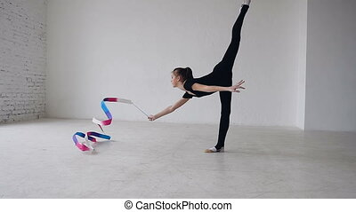 Little gymnastics in black body doing the gymnastics exercise with a colored ribbon in the white studio. Cute girl makes stretching exercise in sport gym