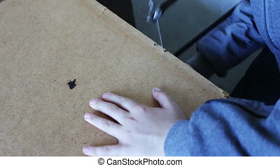 Little handsaw sawing wood veneer - Teenager using a handsaw...