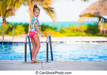 Little happy adorable girl in outdoor swimming pool. Beautiful teenager girl enjoy swimming in pool at tropical exotic hotel outdoors.