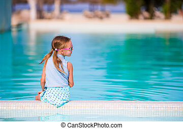 Little happy adorable girl in outdoor swimming pool. Beautiful teenager girl enjoy vacation at tropical exotic hotel outdoors.