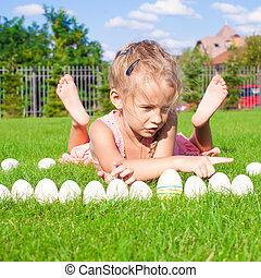 Little happy and funny girl playing with Easter eggs on green grass