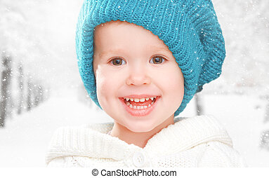 little happy baby child girl in white hat in  winter