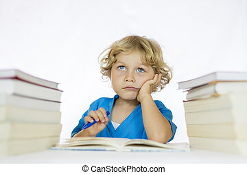 Little happy boy between 4 and 5 years old and thoughtful look sitting at a desk doing his homework, with textbooks on his table