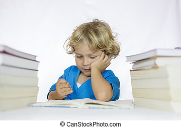 Little happy boy between 4 and 5 years old sitting at a desk doing his homework, with textbooks on his table