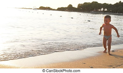 Little happy boy having fun along the beach at the sunset. Slow motion