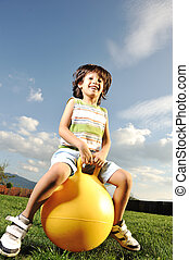 Little happy boy playing with big ball and jumping with slight motion up, scene in park