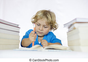 Little happy child between 4 and 5 years old sitting at a desk studying while holding a pencil with textbooks on his table
