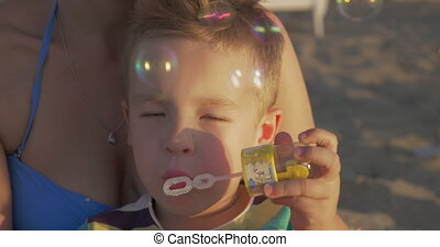 Little happy child blowing bubbles outdoor