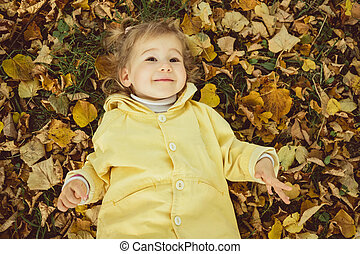 Little happy child lies in the leaves of trees