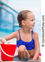 Little happy cute girl with beach toys in outdoor swimming pool