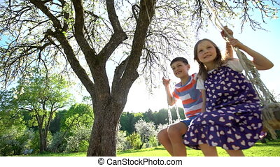 Little happy European children smiling cheerfully while swinging