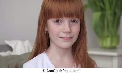 Little happy ginger girl with freckles in a white room