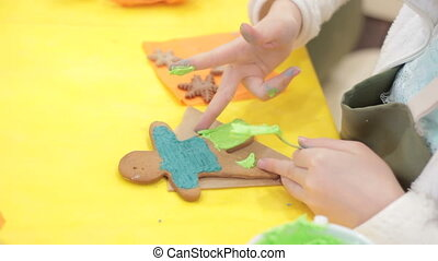 Little happy girl decorates gingerbread cookies