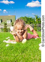 Little happy girl finding Easter eggs on green grass